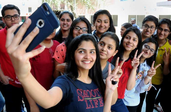 Students take selfies as they celebrate their success after the declaration of CBSE's class XII result, at St Thomas School in New Delhi on Saturday. PTI