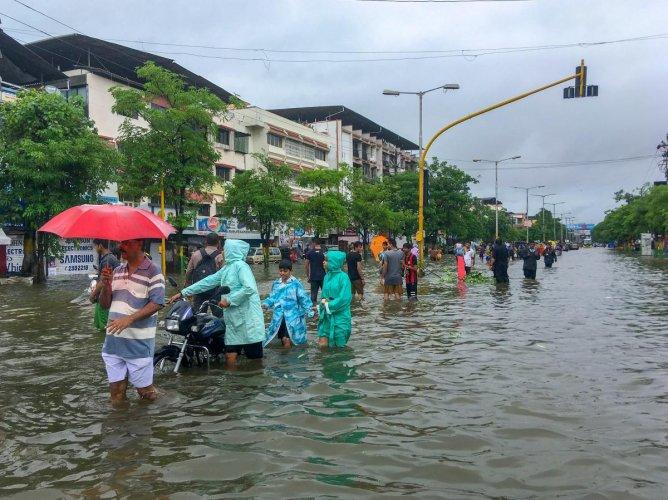 People wade through a flooded street following heavy rains, in Vasai, Maharashtra on Tuesday, 10 July, 2018. (PTI Photo)