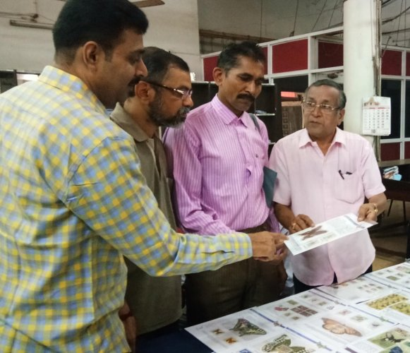 Baikady Shrinivas Rao (extreme right), explains his collection to the visitors during the philatelic exhibition at the head post office in Pandeshwara, Mangaluru, on Sunday.