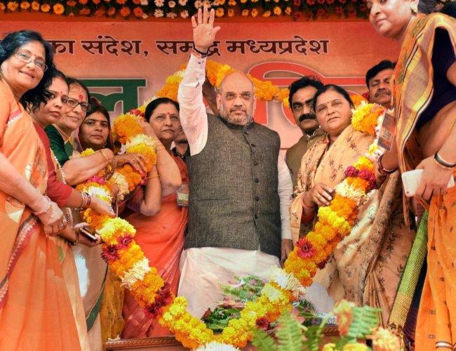 BJP National President Amit Shah being garlanded during 'Mahila Sammelan' function, in Satna. PTI Photo