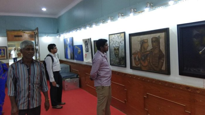 Visitors view paintings during Dasara Art Exhibition at Suchitra Art Gallery on Kalamandira premises in Mysuru on Monday. DH PHOTO