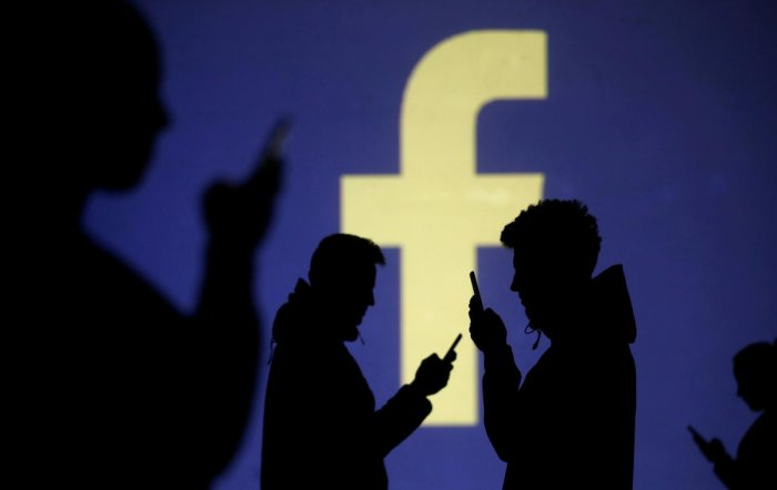 Silhouettes of mobile users are seen next to a screen projection of Facebook logo in this picture illustration. Reuters