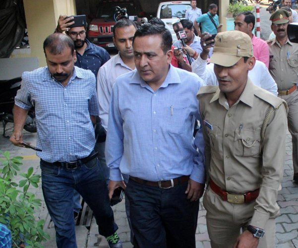 Delhi Police personnel coming out of a house after searching Ashish Pandey, the former Bahujan Samaj Party lawmaker's son at a Posh colony in Lucknow on Tuesday, Oct 16 2018. (PTI Photo)