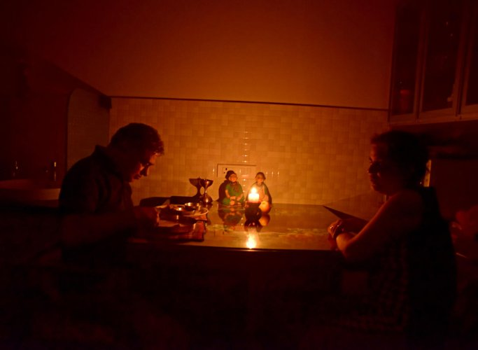 With power connection to their flat disconnected Ramdas Shantaram has dinner by the candlelight, while his wife Veena Shantaram fasting due to Navarathri celebrations watches helplessly. (DH photo/ Govind Raj Javali)