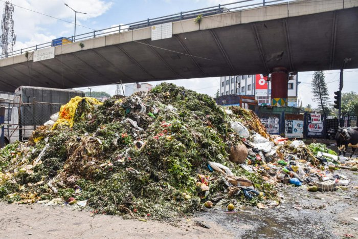 Remains of plantain shoots and mango leaves, unsold flowers and other materials largely used only during festivity dumped after Ayudha Pooja festival at KR Market in Kalasipalya on Friday. DH PHOTOS/S K Dinesh