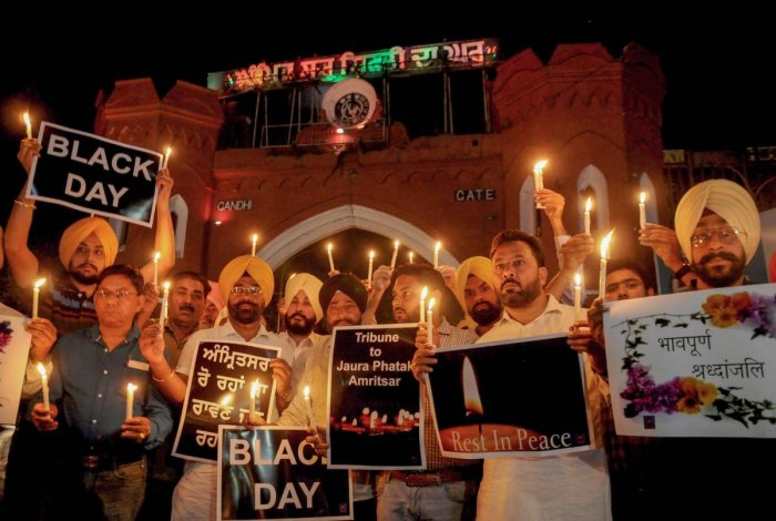 Members of National Human Rights and crime control organisation participate in a candlelight vigil to pay tribute to victims of Amritsar train accident, in Amritsar, Saturday. PTI