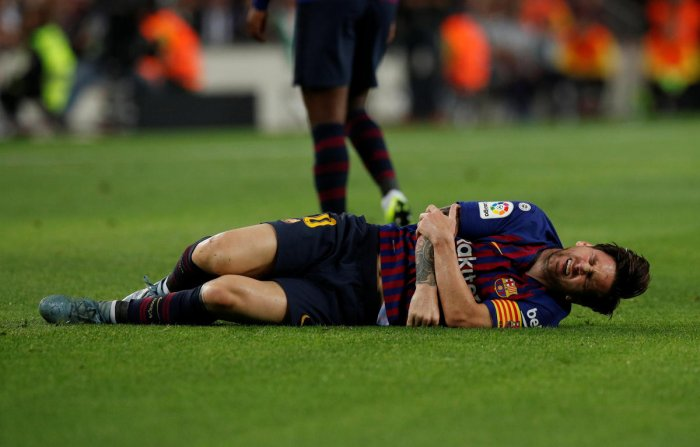 BIG BLOW Barcelona striker Lionel Messi writhes in pain after hurting his right arm during their La Liga clash against Sevilla in Barcelona on Saturday. Reuters