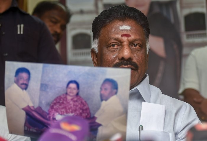 Tamil Nadu Deputy Chief Minister O Panneerselvam shows a photograph which was first meet with AIADMK late Supremo J Jayalalithaa. PTI
