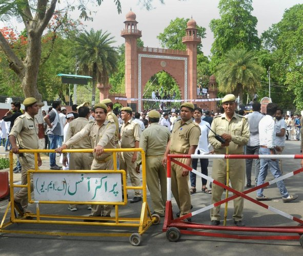 Security personnel stand guard as Aligarh Muslim University students stage a protest over Jinnah portrait issue outside the university gate in Aligarh on Friday. PTI
