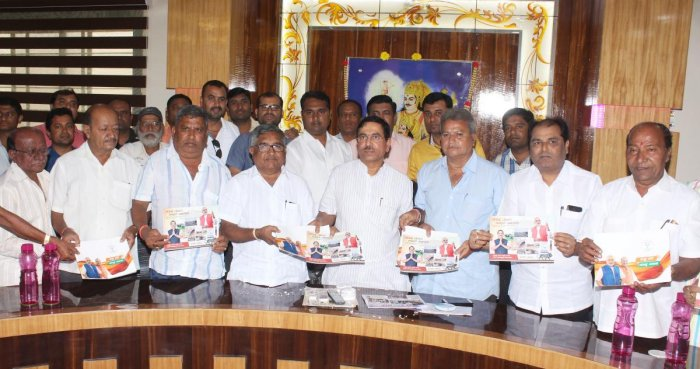 MP Pralhad Joshi distributes booklet on NDA government's achievements, to SSK community leaders, at Kamaripet in Hubballi on Friday.