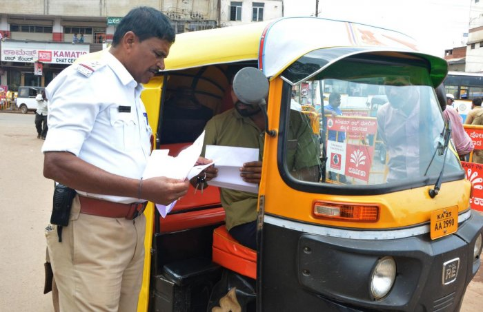 A traffic police check documents of an autorickshaw at Chennamma Circle area in Hubballi on Friday, during the autorickshaw checking drive.