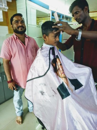 Sanjay Mahale oversees the`free' hair cut given to a student from DK ZP higher primary school at his Kudla Mens professional saloon in Bikarnakatte.