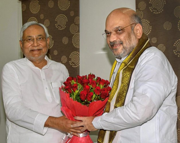Bihar Chief Minister Nitish Kumar and Bharatiya Janata Party (BJP) President Amit Shah exchange greetings at the state guest house, in Patna on Thursday. (PTI Photo)