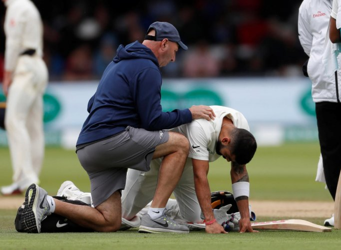 Indian captain Virat Kohli receives treatment from medical staff for a back injury. Reuters