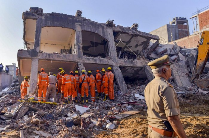 Rescue workers search for survivors under the debris of a collapsed building at Shahberi village, in Greater Noida West on Wednesday, July 18, 2018. A six-storey under-construction building collapsed in Greater Noida, killing at least two persons and trapping several others under the debris. (PTI Photo)