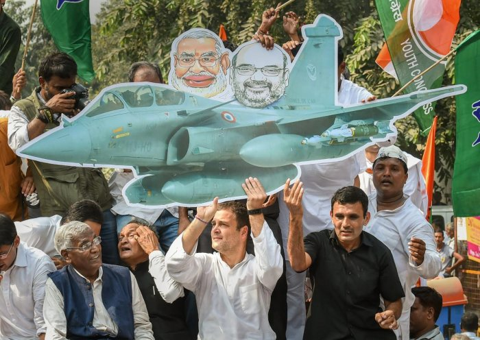 Congress president Rahul Gandhi holds a cutout of a fighter aircraft during a protest demanding the reinstatement of CBI Director Alok Verma outside the CBI headquarters, in New Delhi, on Friday. PTI