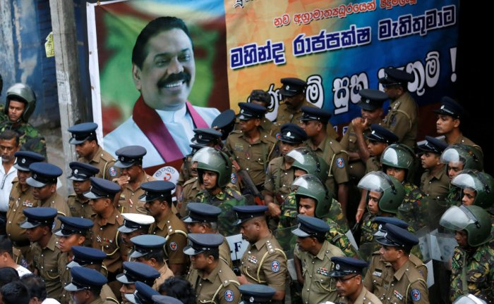 Members of Sri Lanka's Special Task Force and the police stand guard next to a poster of newly appointed Prime Minister Mahinda Rajapaksa after an official security guard of sacked minister Arjuna Ranatunga shot and wounded three people in front of the Ceylon Petroleum Corporation, in Colombo, Sri Lanka October 28, 2018. REUTERS