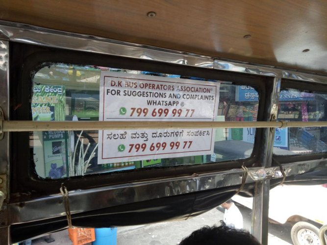 A sticker inside a private city bus in Mangaluru encouraging passengers to lodge complaints and pictures on the WhatsApp helpline.
