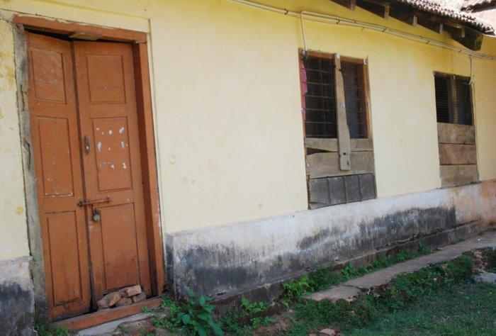 The broken door and windows of the Government First Grade College building in Madikeri.