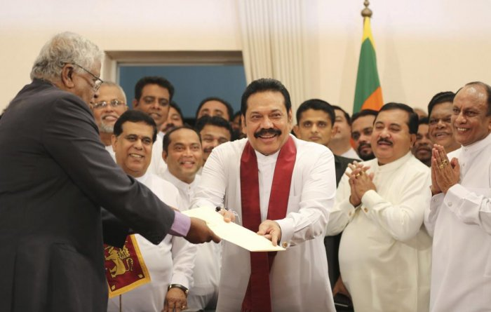 Sri Lanka's newly appointed prime minister Mahinda Rajapaksa, center, hands over inaugural documents to an official during his duties assuming ceremony in Colombo, Sri Lanka, Monday, Oct. 29, 2018. AP/PTI