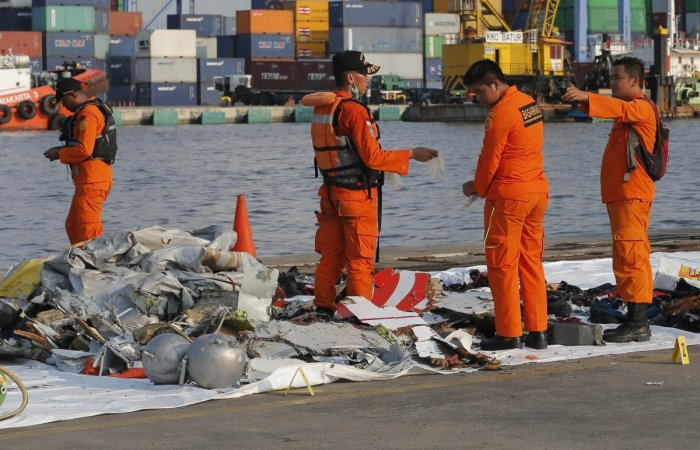 Members of Indonesian Search and Rescue Agency (BASARNAS) inspect debris recovered from near the waters where a Lion Air passenger jet is suspected to crash, at Tanjung Priok Port in Jakarta, Indonesia. (AP/PTI File Photo)