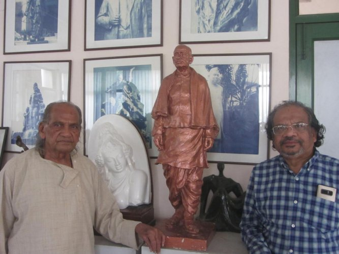 Ram Sutar and son Anil Sutar with a three-foot model of the Statue of Unity.