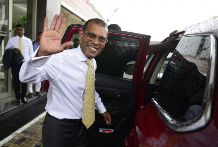 Former president of the Maldives Mohamed Nasheed waves as he leaves an apartment building as he prepares to return to the Maldives. AFP Photo