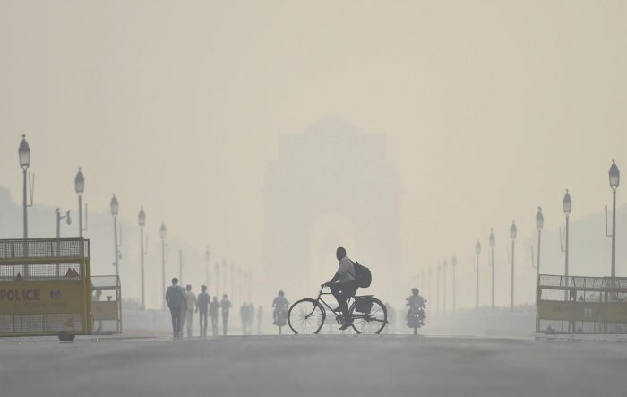 A cyclist rides through the heavy haze at Rajpath in New Delhi. About 44 joint teams from various agencies will be deployed to check air pollution in the national capital as the air quality in the city nosedived to 'severe' category. (PTI Photo)