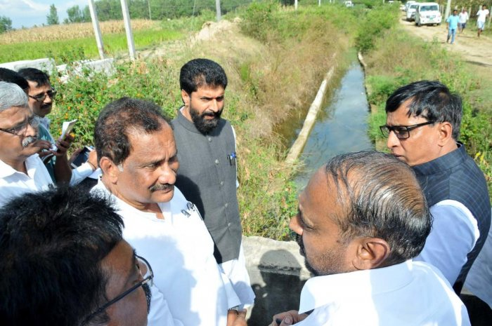 MLC S L Dharme Gowda explains the condition of Karagada canal to District In-charge Minister K J George.