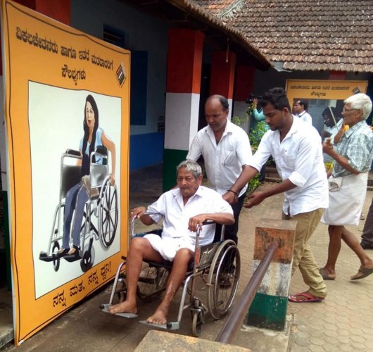 A physically challenged voter is being offered a wheelchair at a polling booth in Byndoor.