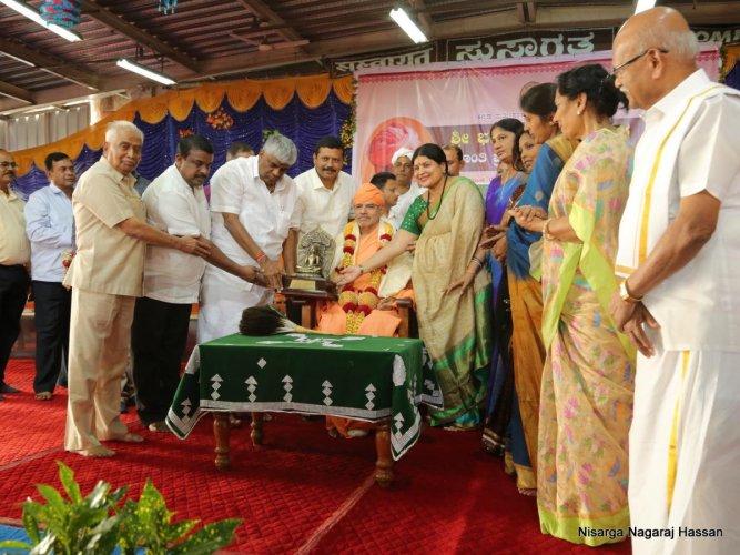 Kannada and Culture MinisterJayamala,confers the Bhagawan Mahaveer Peace Award on Charukeerti Bhattaraka Swami of Shravanabelagola in Hassan,on Sunday. DH PHOTO