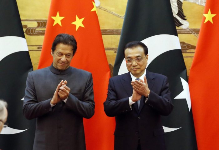 Pakistan Prime Minister Imran Khan, left, and China's Premier Li Keqiang attend a signing ceremony at the Great Hall of the People in Beijing. PTI