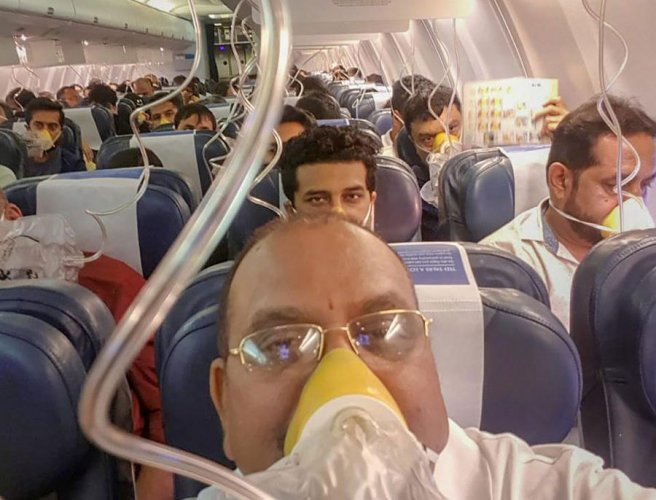 Passengers on board the Mumbai-Jaipur Jet Airways flight wear oxygen masks during an emergency after cabin pressure drop, in Mumbai, Thursday. PTI file photo