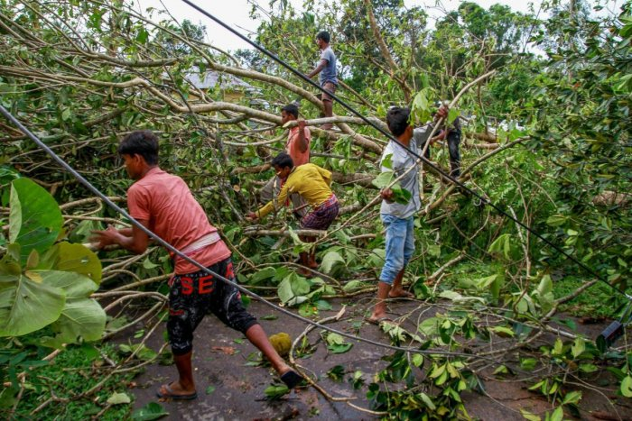 Residents try to clear the road after a cyclone hit Belchharra village at Khowai district of Tripura on Monday. PTI Photo