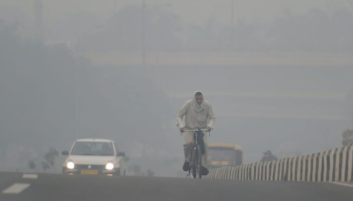 A cyclist rides through heavy haze, in New Delhi. PTI photo