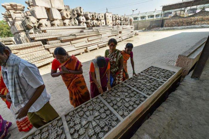 Visitors look at chiseled slabs of stone for a Ram temple at Kar Sevak Puram workshop in Ayodhya on Monda. PTI file photo