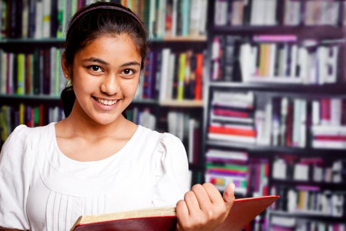 Indian Teenager Girl studying in a Library with BookshelfEducation, Student