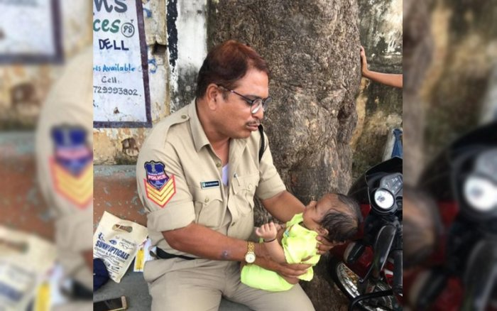 Telangana cop Mujeeb Ur Rehman with the toddler outside the examination centre. (DH Photo)