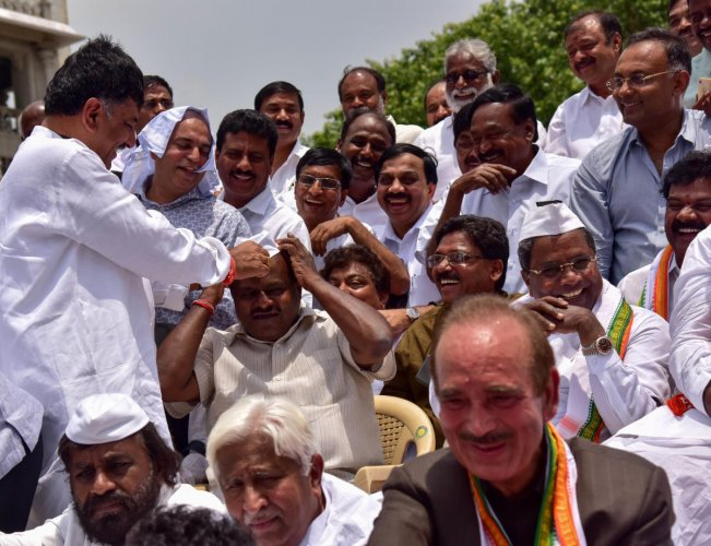 Congress leader D K Shivakumar puts a cap on the head of JD(S) state president H D Kumaraswamy as other Congress leaders look on during a joint protest at the Vidhana Soudha in Bengaluru on Thursday. dh photo
