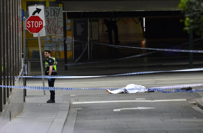 A policeman stands near a body covered with a sheet near the Bourke Street mall in central Melbourne. Reuters photo