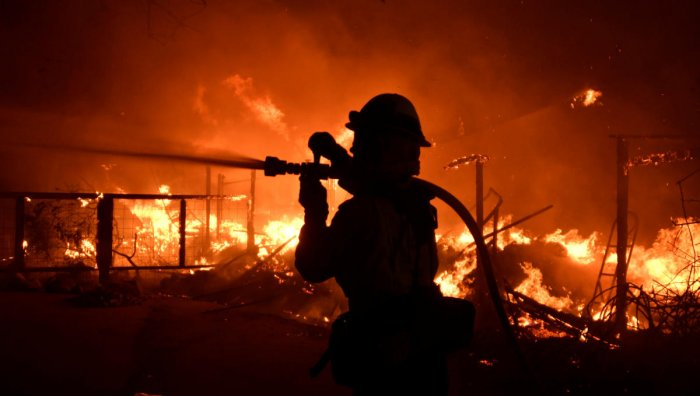 A firefighter hoses down a property engulfed in flames during the Woosley Fire in Malibu, California. (Reuters Photo)
