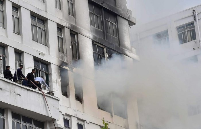 Smoke billows out of a window after a fire broke out on the fifth floor of a high-rise office building at Park Street, in Kolkata on Monday. PTI