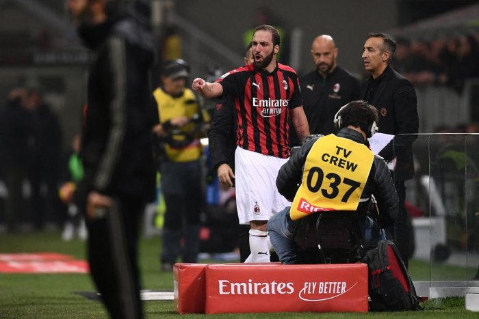 AC Milan's Argentine forward Gonzalo Higuain reacts from the side of the pitch after he received a red card during the Italian Serie A football match AC Milan vs Juventus. AFP