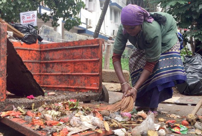 A pourakarmika collects waste at Indiranagar on Wednesday. DH Photo/Grace Hauck