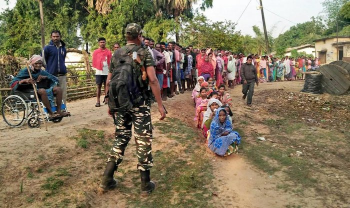People wait to cast votes at a polling station in the Maoist-hit Sukma district on Monday. PTI
