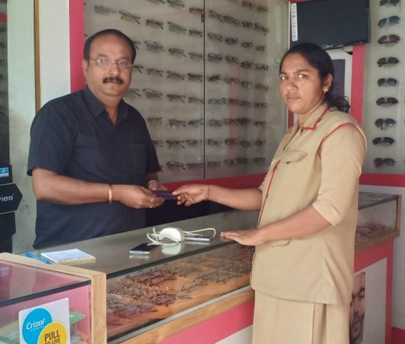 Postwoman Vinaya opens an IPPB account and hands over IPPB's QR card to a shopkeeper in Chikkamagaluru.
