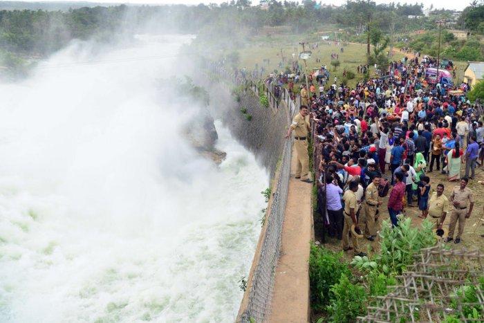 Tourists take a glimpse of water gushing out of the KRS damin Srirangapatna taluk, Mandya district, on Sunday. DH PHOTO