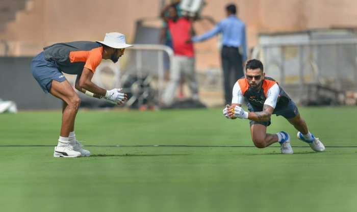 Indian captain Virat Kohli (right) takes a catch during a practice session as KL Rahul looks on in Hyderabad on Thursday. PTI