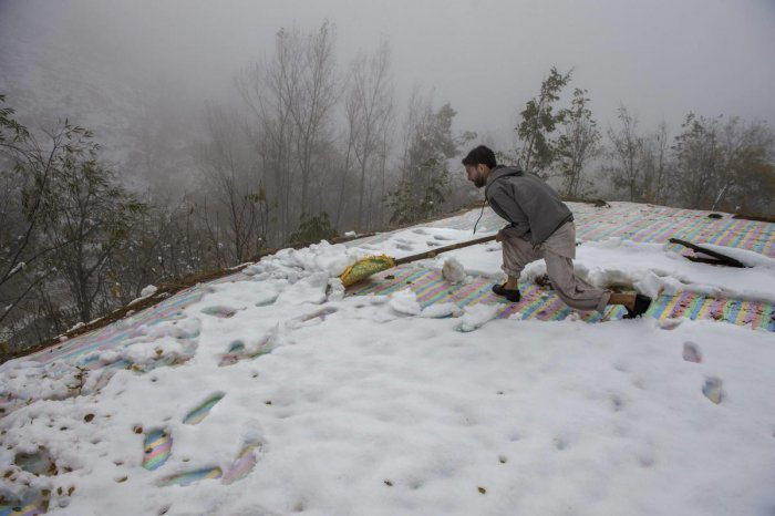 A man clears snow from the roof top of his mud-house on the out skirts of Srinagar. PTI