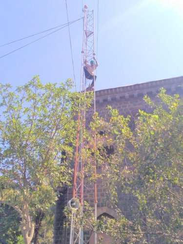 A protesting sugarcane Belagavi farmer climbs up a mobile tower to draw government's attention to farmers' plight on Friday. DH photo.